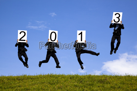 businessman holding 2013 and jumping