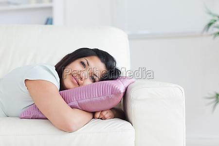 kobieta relaks na kanapie trzymajac poduszke