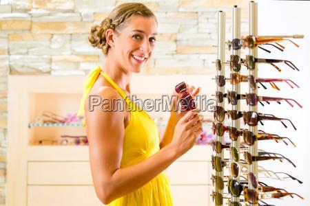 mloda kobieta w optyk kupuje okulary