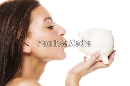 beautiful young woman kissing piggy bank