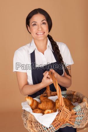 happy woman carrying fresh croissants