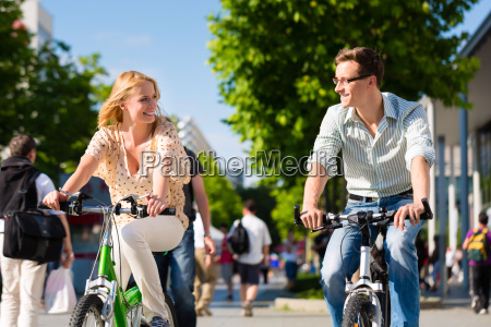 couple in city driving with bicycle