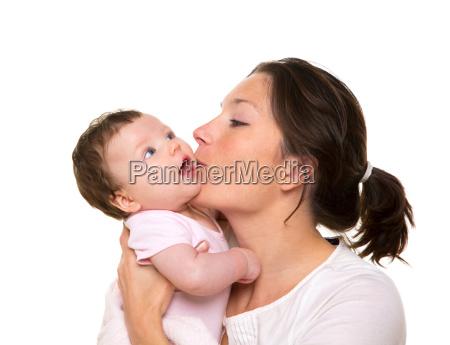 beautiful mother kissing baby girl hug