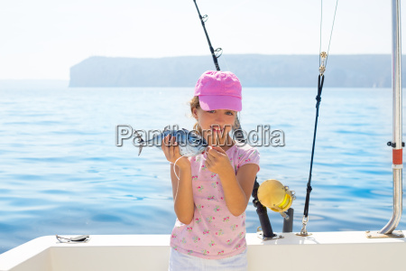 child little girl fishing in boat