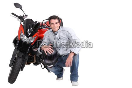 czlowiek kucajac obok motocykla