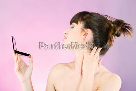 kobieta sprawdzanie skory twarzy w lustro