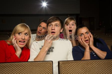 przerazeni ludzie siedza siedziec w kinie