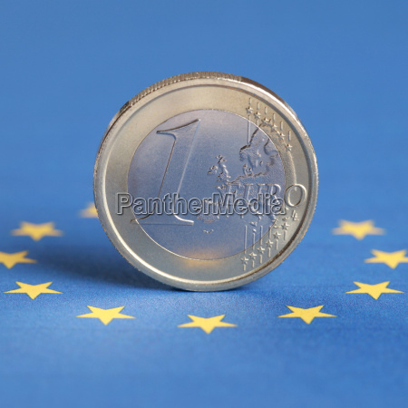 one euro coin on eu flag