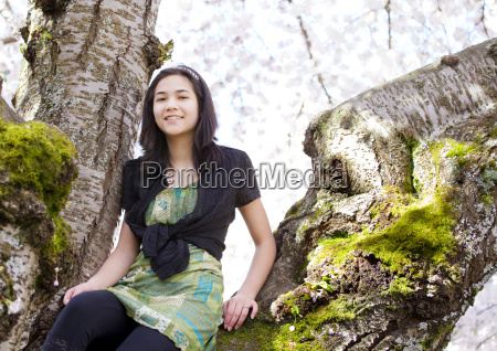 young teen girl sitting on branches