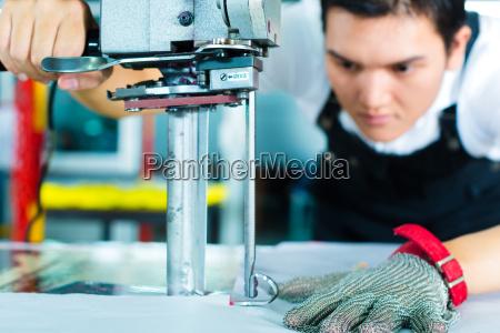 pracownicy fabryki przy maszynie w fabryce