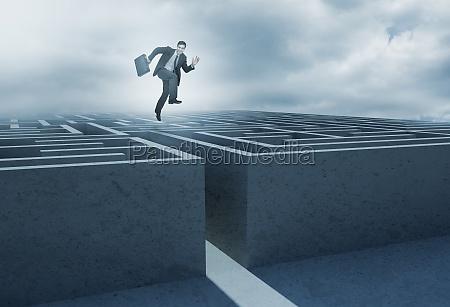 biznesmen skaczacy nad labiryntem