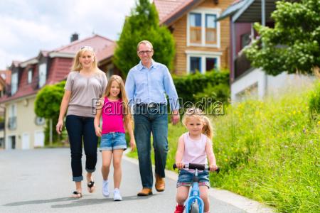 rodzina bierze spacer po dzielnicy mieszkalnej