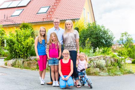 szczesliwa rodzina przed domem rodzinnym
