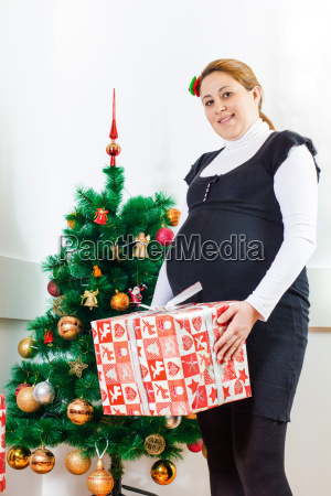 happy pregnant woman holding a christmas