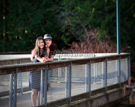 young interracial couple standing on bridge