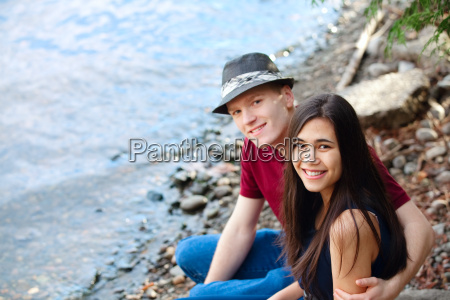 beautiful young interracial couple sitting together