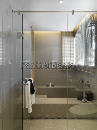 large bathtub behind glass wall and