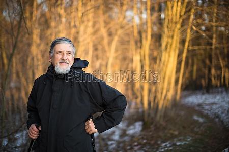 starszy mezczyzna nordic walking cieszac sie