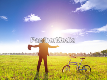 businessman relaxing in green land and