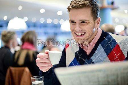 smiling man reading newspaper at restaurant