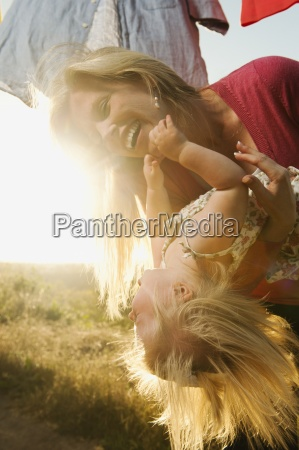 carrying laughing mother daughter playful backlit