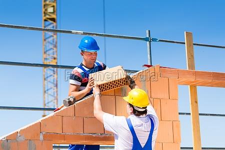dwoch pracownikow budowlanych na placu budowy