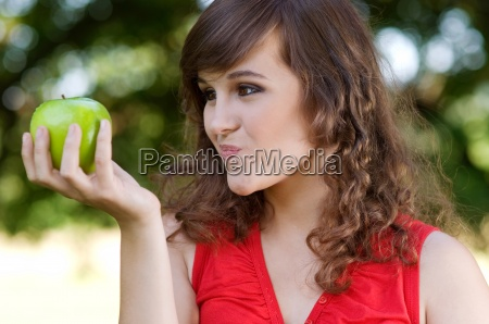 young woman wondering about eating apple