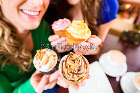 kobiety jedza babeczki podczas picia kawy