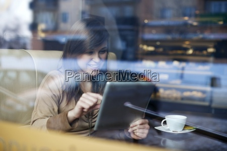 young woman using tablet in coffee