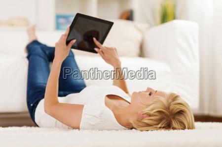 blonde woman using digital tablet