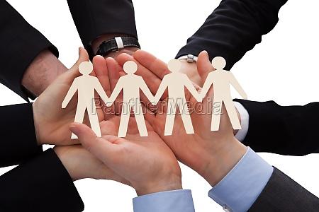 biznesmeni trzymanie ludzkiej figury wycinka
