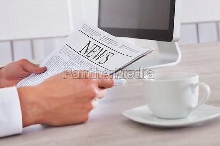 czlowiek trzyma gazety