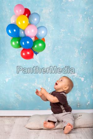 maly chlopiec bawi sie z balonow
