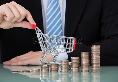 biznesmen z koszykiem i monety stacks