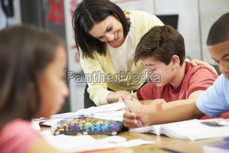 nauczyciel pomagajacy uczniom studiowac w biurkach