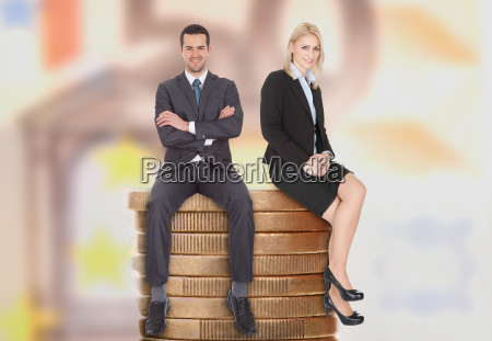 biznes ludzie siedzacy na ulozone monety