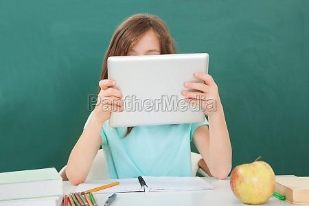 schoolgirl using digital tablet against chalkboard