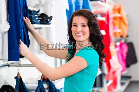 kobieta kupuje ubrania w sklepie