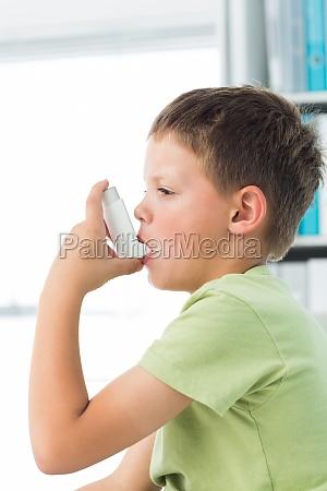chlopiec przy uzyciu inhalatora astmy w