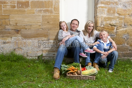 happy family sitting together outdoors with