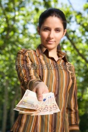 offering wad of banknotes woman