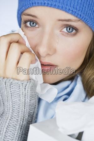 mloda kobieta placze wycierajac lzy chusteczka