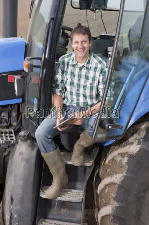 farmer sitting in cab of tractor
