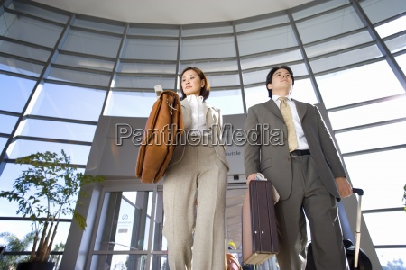 businessman and woman walking with luggage