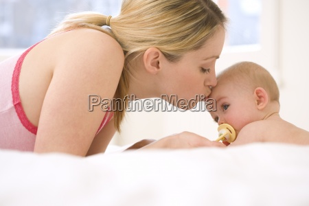 mother kissing baby girls 9 12