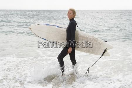 kobieta surfer w plytkiej wodzie na