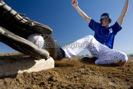 baseballista w niebieskim mundurze slizgasie do