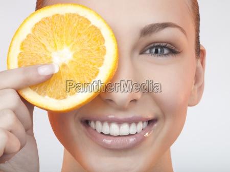 kobieta trzymala kawalek pomaranczy przed oczami