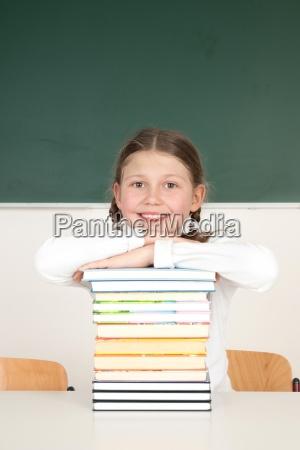 uczennica opierajac sie na stos ksiazek