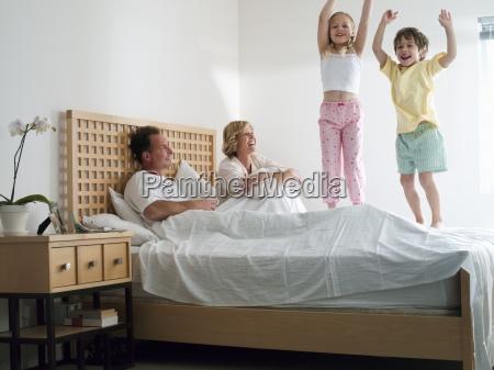 rodzice lezace w podwojnym lozku w